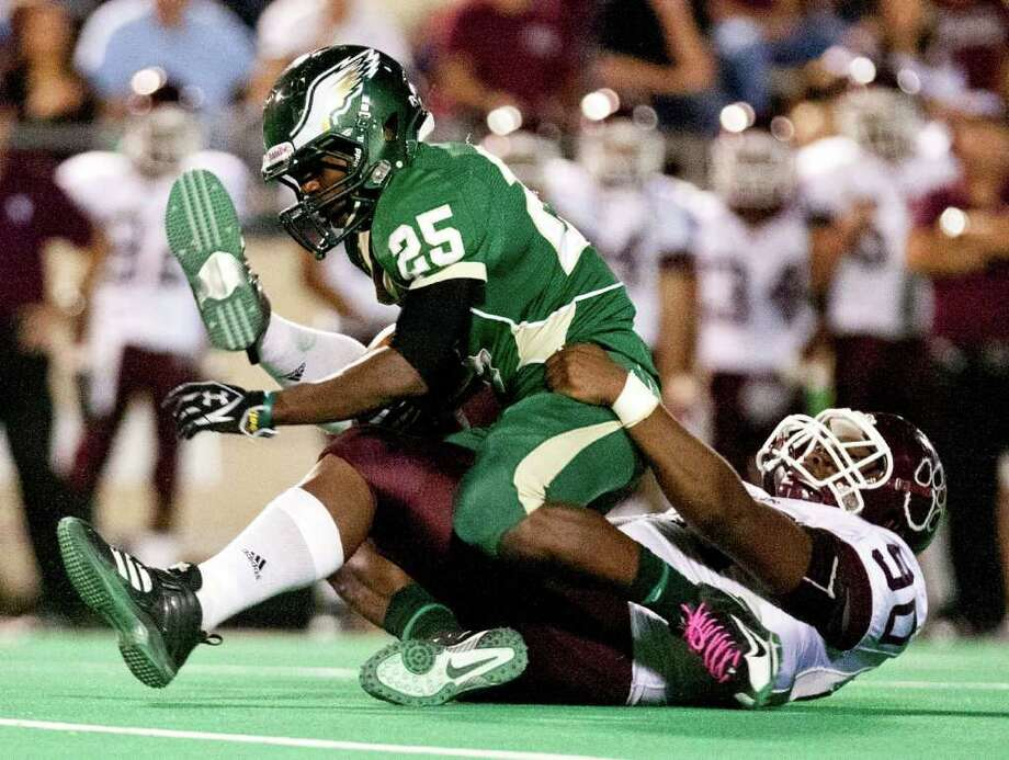 10/14/11: Running back G. Gladney  of the Cy Falls Eagles is brought down for a loss by defensive tackle Ross Donelly #90 of the Cy Fair Bobcat's   in a high school District 17-5A football game at Pridgeon Stadium in Houston, Texas. For to Chronicle :Thomas B. Shea Photo: For To Chronicle :Thomas B. Shea