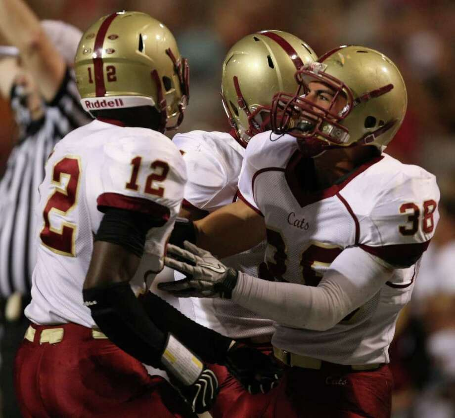 Cy-Woods' Alfred Pullom (12) is congratulated by teammate Ryan Renaud after Pullom's tackle during the first half of their District 17-5A matchup against Langham Creek, Friday, October 14, 2011 at Berry Center in Cypress. Photo: Eric Christian Smith, For The Chronicle