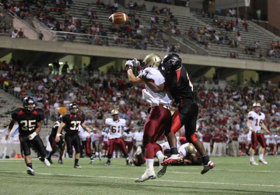Langham Creek's Jeremy land (right) breaks up a touchdown pass intended for Cy-Woods' Gary Tesch during the first half of their District 17-5A matchup, Friday, October 14, 2011 at Berry Center in Cypress. Photo: Eric Christian Smith, For The Chronicle
