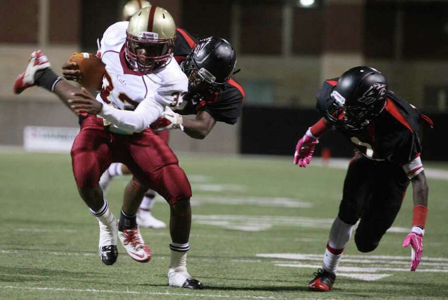 Cy Woods 50, Langham Creek 44Cy Woods' Jeffrey Bogan (33) shakes off a Langham Creek defender for a touchdown  as Jeremy Land looks on during the first half of their District 17-5A matchup, Friday, October 14, 2011 at Berry Center in Cypress. Photo: Eric Christian Smith, For The Chronicle
