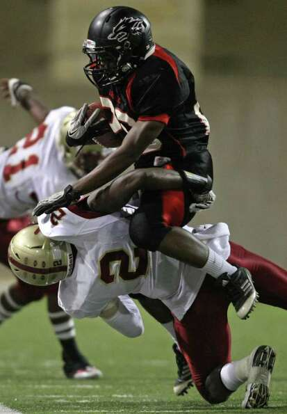 Langham Creek's Jeremiah Williams (right) is tackled by Cy-Woods' Jamaul Tompkins during the first h