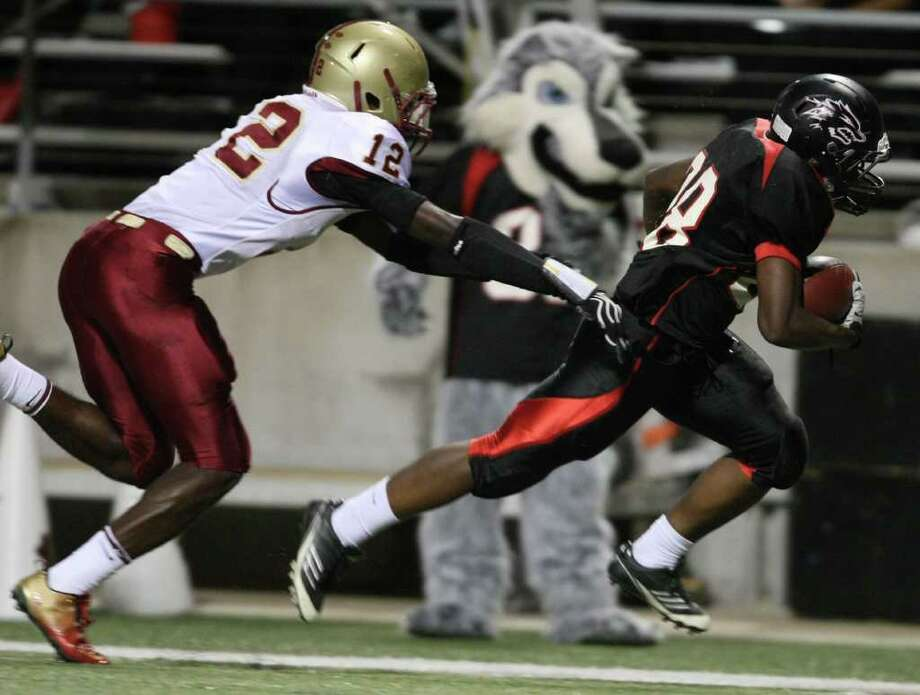Langham Creek's Jeremiah Williams (right) scampers past Cy-Woods' Alfred Pullom for a 39-yard touchdown run during the first half of their District 17-5A matchup, Friday, October 14, 2011 at Berry Center in Cypress. Photo: Eric Christian Smith, For The Chronicle