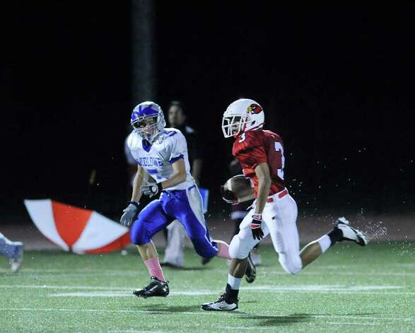 At right, Joel Arroyo, # 3 of Greenwich, returns a kickoff while being pursued by Jack Bradley, # 5 of Fairfield Ludlowe High School during football game between Greenwich High School and Fairfield Ludlowe High School at Greenwich, Friday night, Oct. 14, 2011. Photo: Bob Luckey / Greenwich Time