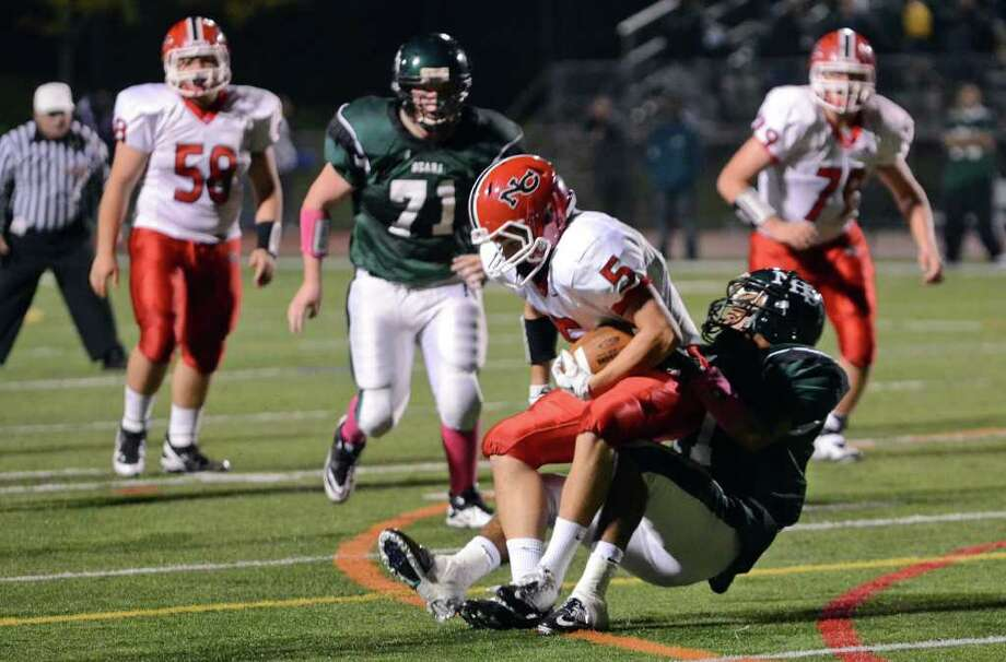 New Canaan's Jack Barfuss (5) is brought down by Norwalk's Derek Edwards (11) during the football game at Norwalk High School on Friday, Oct. 14, 2011. Photo: Amy Mortensen / Connecticut Post Freelance