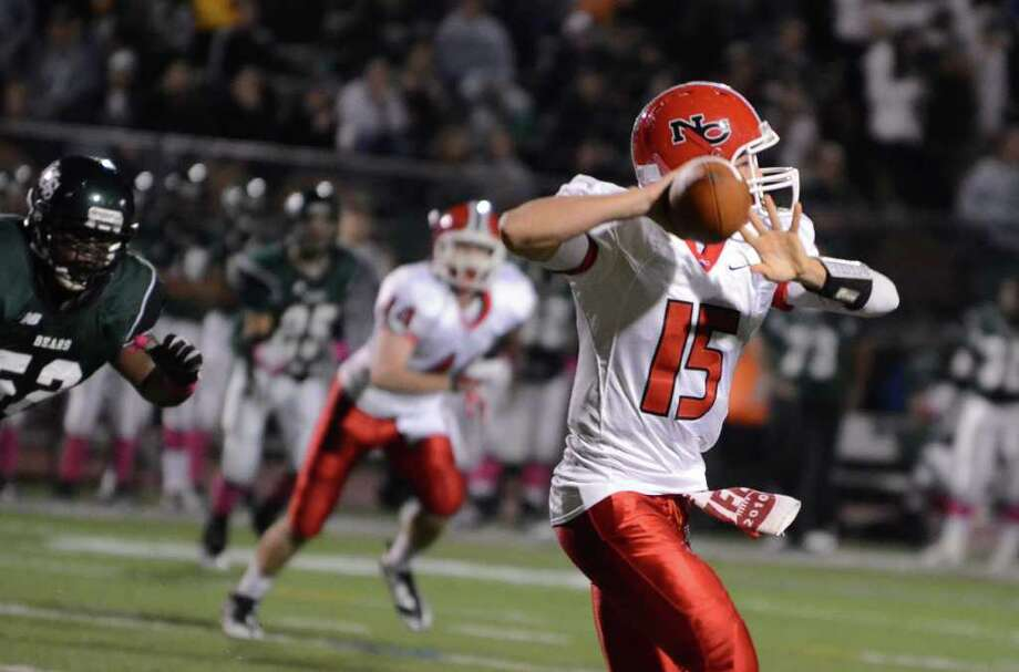 New Canaan's quarterback Matt Milano (15) throws a pass during the football game against Norwalk at Norwalk High School on Friday, Oct. 14, 2011. Photo: Amy Mortensen / Connecticut Post Freelance