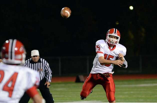 New Canaan's quarterback Matt Milano (15) throws a pass to teammate Patrick Newton (24) during the football game against Norwalk at Norwalk High School on Friday, Oct. 14, 2011. Photo: Amy Mortensen / Connecticut Post Freelance