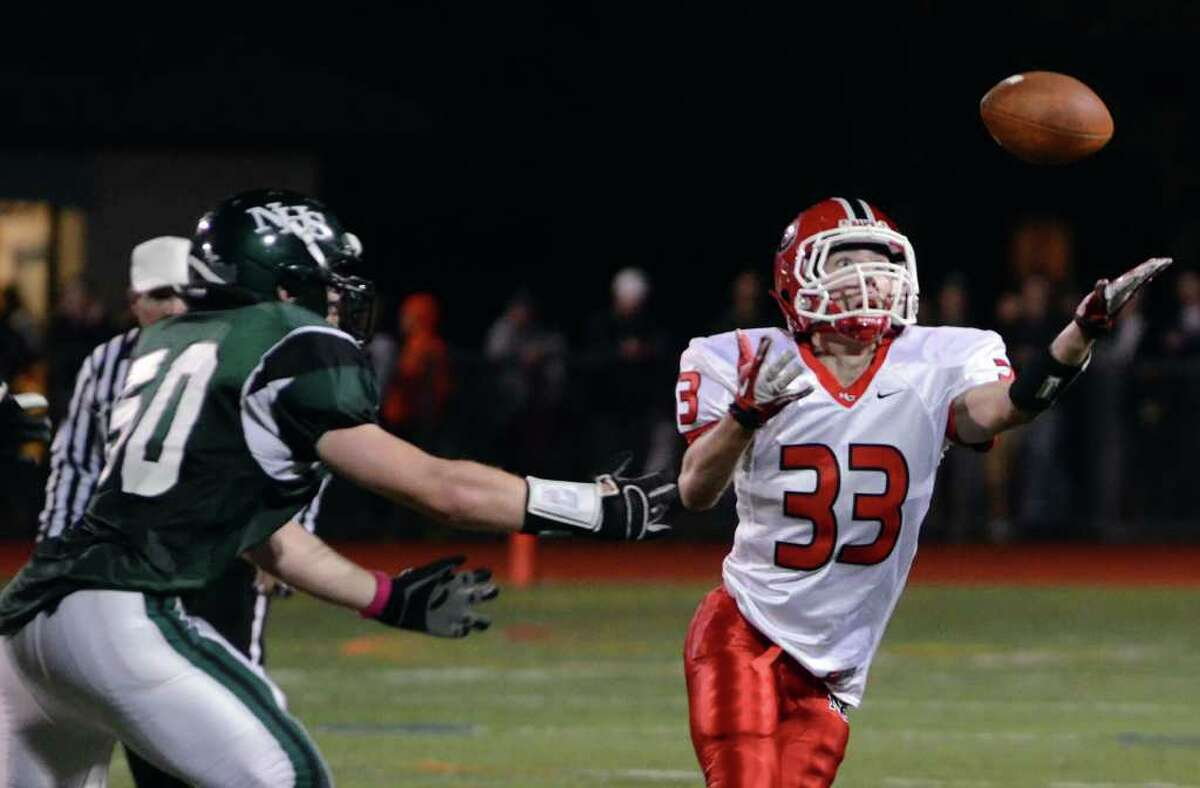 New Canaan's Louis Hagopian (33) reaches for the ball during the football game against Norwalk at Norwalk High School on Friday, Oct. 14, 2011.