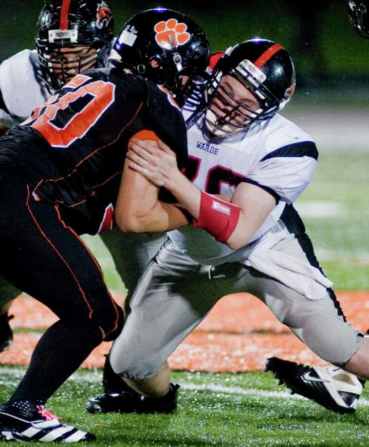 Ridgefield High School's Andrew Barton, left, and Fairfield Warde's John McKeown square off during a football game at Ridgefield. Friday, Oct. 14, 2011 Photo: Scott Mullin / The News-Times Freelance