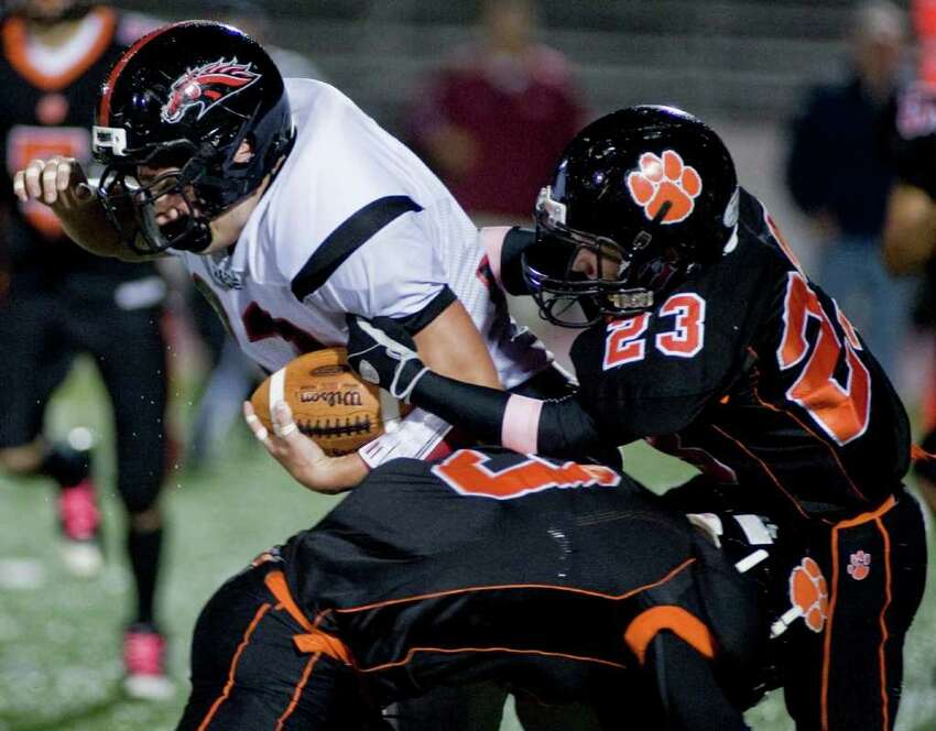 Fairfield Warde's David Wolff, left, tries to get away from Ridgefield High School's Micky Hicks during a football game at Ridgefield. Friday, Oct. 14, 2011