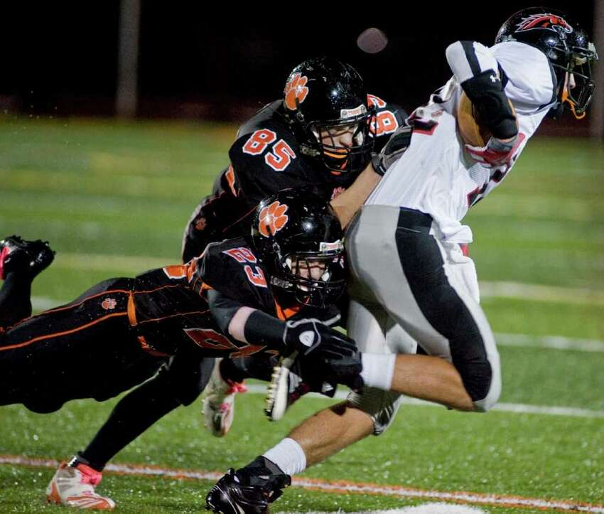 Ridgefield High School's Micky Hicks, left, and Timo Muro try to take down Fairfield Warde's Devon Lofton during a football game at Ridgefield. Friday, Oct. 14, 2011