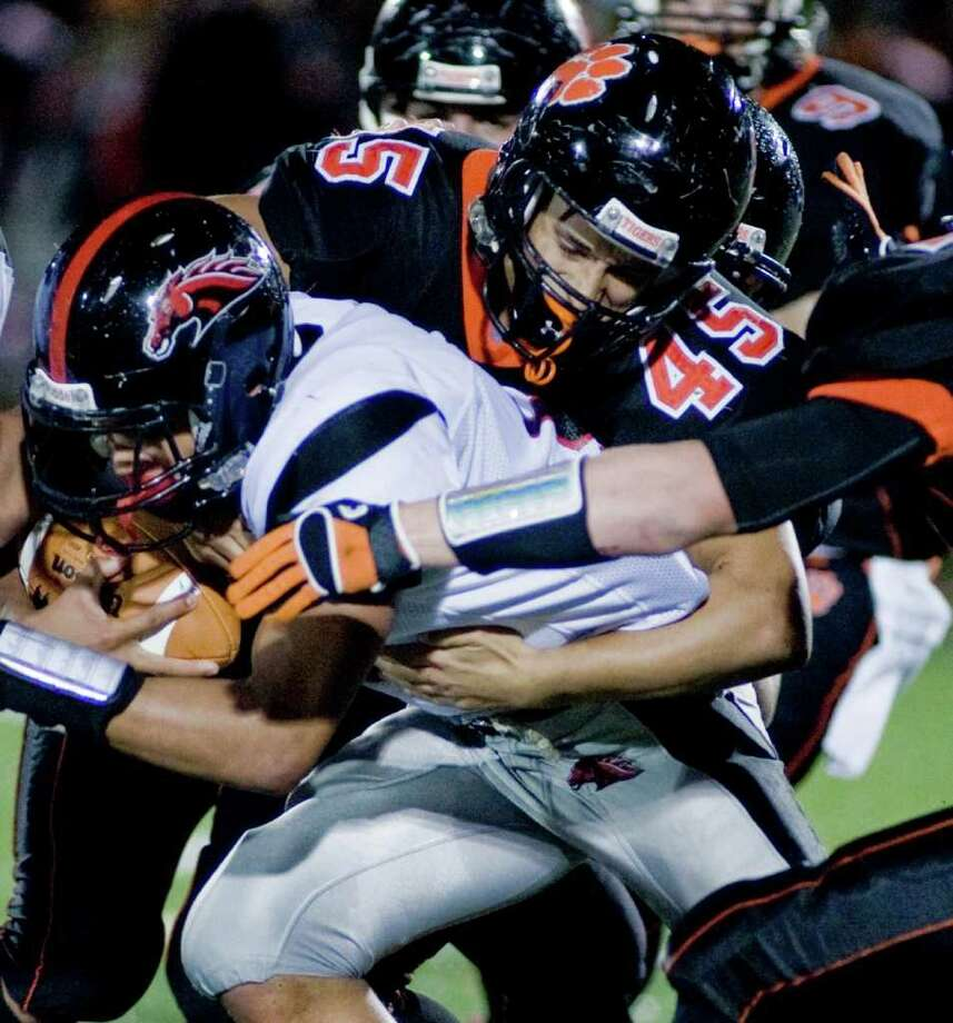 Ridgefield High School's Victor Fernandez tries to take down the Fairfield Warde runner in a football game played at Ridgefield. Friday, Oct. 14, 2011 Photo: Scott Mullin / The News-Times Freelance