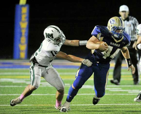 New Milford's Matt Sheehy, left, tries to bring down Newtown running back Louis Fenaroli during their game at Newtown High School on Friday, Oct. 14, 2011.  Newtown won 37-14. Photo: Jason Rearick / The News-Times
