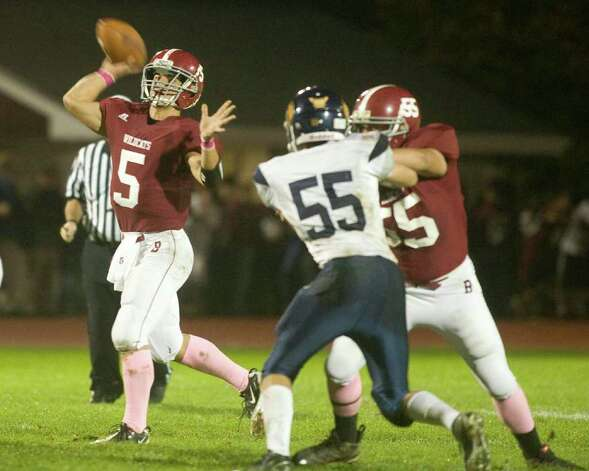Bethel High School quarterback Brandon Schmidt (5)  gets good protection from offensive lineman John Dias as he fires a pass downfield during an SWC football game against Weston High School Friday night, Oct. 14, 2011, at Bethel High School. Photo: Barry Horn / The News-Times Freelance