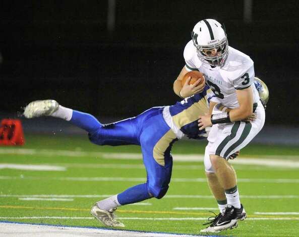 Newtown's Mike Lord, left, tries to bring down New Milford quarterback Connor Shanahan during their game at Newtown High School on Friday, Oct. 14, 2011.  Newtown won 37-14. Photo: Jason Rearick / The News-Times