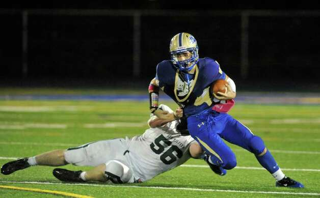 New Milford's Blaze Martin, left, brings down Newtown quarterback Andrew Tarantino during their game at Newtown High School on Friday, Oct. 14, 2011.  Newtown won 37-14. Photo: Jason Rearick / The News-Times