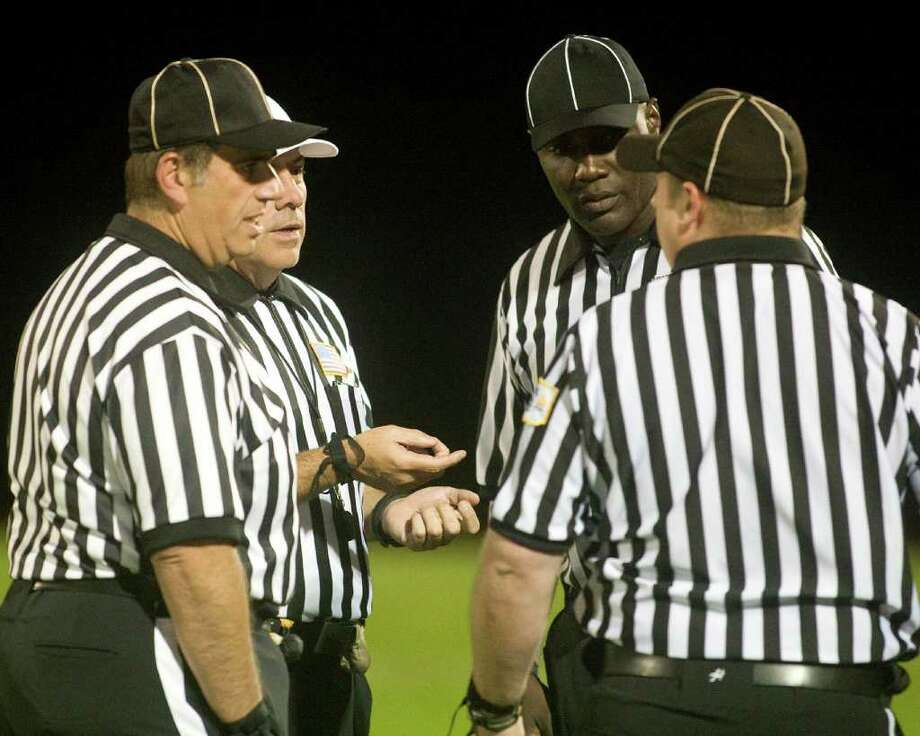 The officials huddle before the SWC football game which matched Bethel High School and Weston High School Friday night, Oct. 14, 2011, at Bethel High School. Photo: Barry Horn / The News-Times Freelance