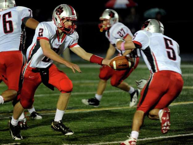 Pomperaug QB #2 Eric Beatty, left, hands off the ball to #5 Matt Paola, during boys football action against Bunnell in Stratford, Conn. on Friday October 14, 2011. Photo: Christian Abraham / Connecticut Post