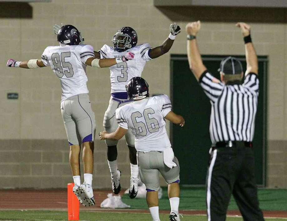 Warren's Jarred Owens (03) celebrates a 47-yard touchdown run with teammates Juan Montemayor (85) and Daniel Blanco (66) against Holmes in high school football at Gustafson Stadium on Friday. Photo: Kin Man Hui, -- / San Antonio Express-News