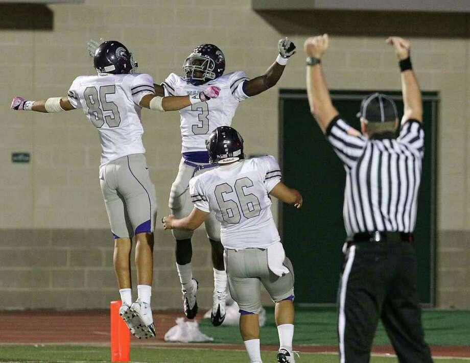 Warren's Jarred Owens (03) celebrates a 47-yard touchdown run with teammates Juan Montemayor (85) and Daniel Blanco (66) against Holmes in high school football at Gustafson Stadium on Friday. Photo: Kin Man Hui, -- / San Antonio Express-News