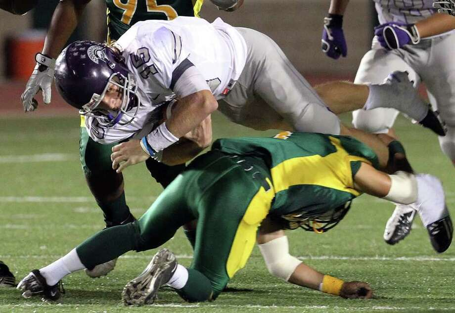 Warren quarterback Rex Dausin (15) dives for extra yardage against Holmes' Moses Berrones (03) in high school football at Gustafson Stadium on Friday, Oct. 14, 2011. Kin Man Hui/kmhui@express-news.net Photo: Kin Man Hui, -- / San Antonio Express-News