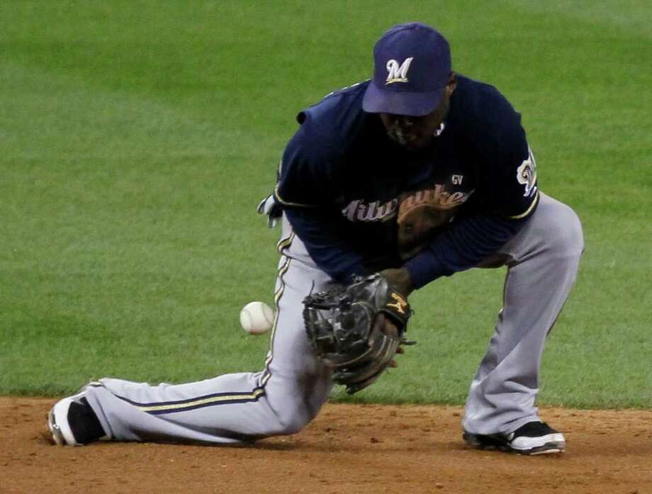 Milwaukee Brewers shortstop Yuniesky Betancourt can't handle a ball hit by St. Louis Cardinals' Jon Jay during the sixth inning of Game 5 of baseball's National League championship series Friday, Oct. 14, 2011, in St. Louis. (AP Photo/Charles Rex Arbogast) Photo: Charles Rex Arbogast, Associated Press / AP