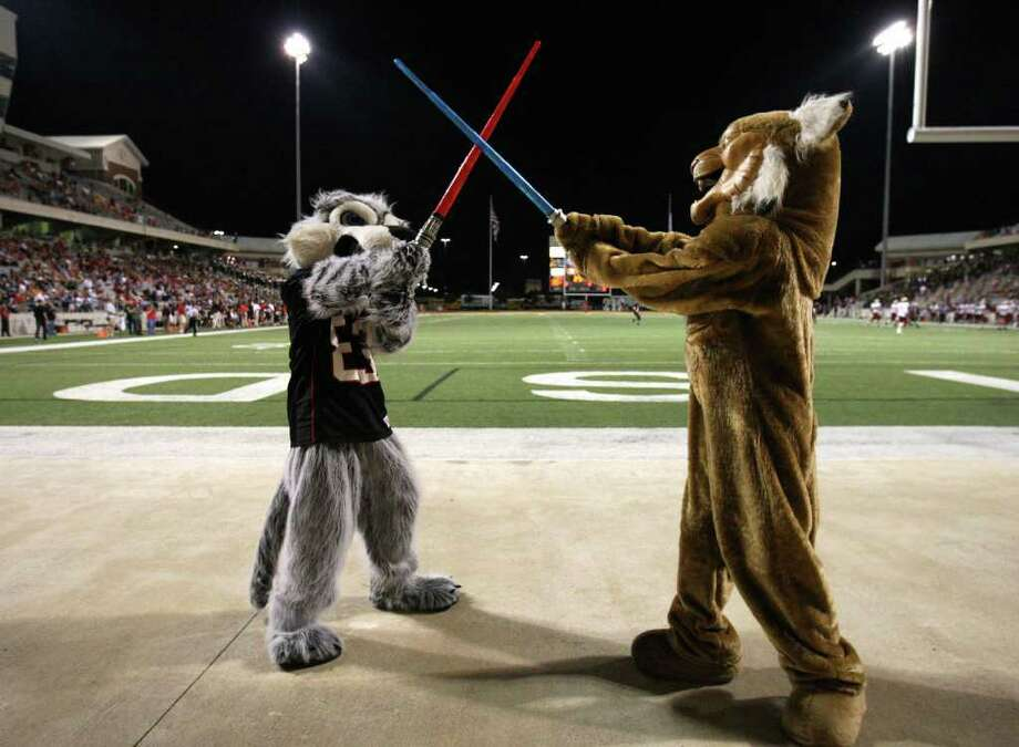 Langham Creek mascot Josh Attra (left) sword fights with Cy=Woods mascot Alex Whitnah during the second half of their District 17-5A matchup, Friday, October 14, 2011 at Berry Center in Cypress. Photo: Eric Christian Smith, For The Chronicle