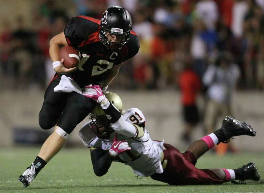 Langham Creek's Connor Feist (12) escapes the tackle of Cy-Woods' Jordan Cipriani during the second half of their District 17-5A matchup, Friday, October 14, 2011 at Berry Center in Cypress. Photo: Eric Christian Smith, For The Chronicle