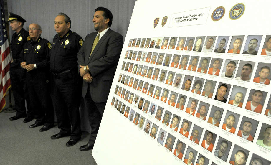 Police Chief William McManus (from left), Sheriff Amadeo Ortiz, Chief Deputy Sheriff Manuel Longoria and ATF's Bart Mora show photos of those arrested in Operation Triple Beam. Photo: BILLY CALZADA/gcalzada@express-news.net