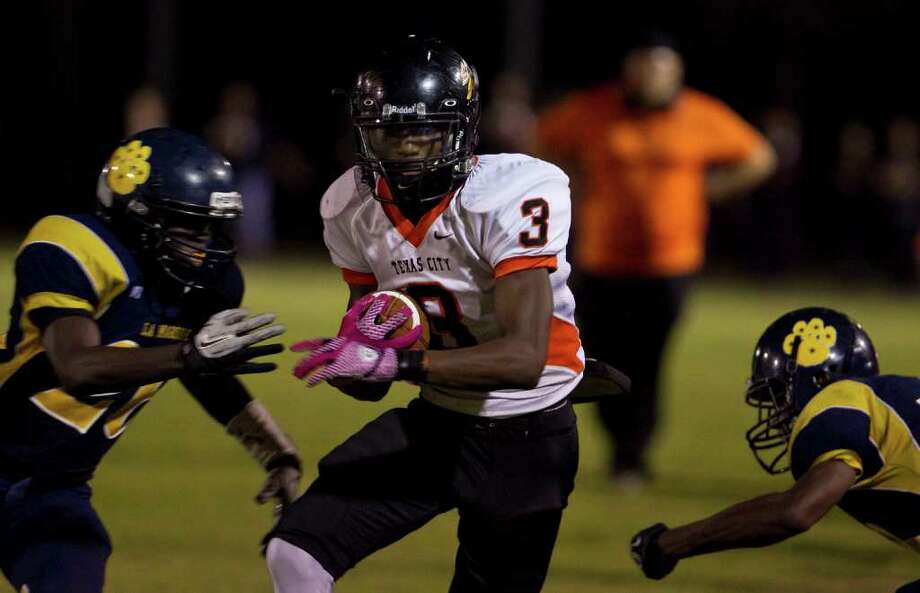 Texas City High School's Leonard Brooks, center, looks for running room as La Marque High School's Demetris Branch, left, closes in during the third quarter of a 24 4-A high school football game at Etheredge Stadium, Friday, Oct. 14, 2011,  in La Marque. Photo: Nick De La Torre, Houston Chronicle / © 2011  Houston Chronicle