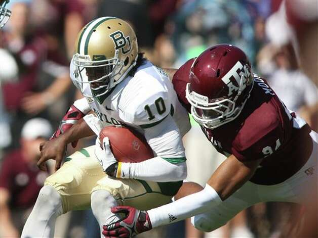 Texas A&M's Damontre Moore (94) sacks Baylor's Robert Griffin III during the first half of an NCAA college football game Saturday, Oct. 15, 2011, in College Station, Texas. (AP Photo/Jon Eilts) Photo: Jon Eilts, Associated Press / FR170396 AP