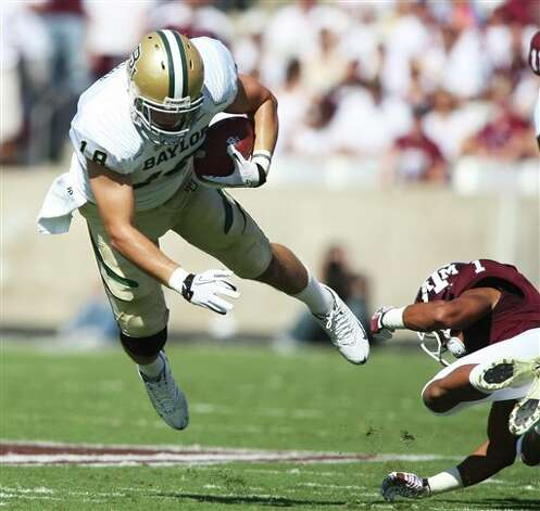 Baylor's Jordan Najvir, left, dives over Texas A&M defender Trent Hunter, right, during the first half of an NCAA college football game Saturday, Oct. 15, 2011, in College Station, Texas. (AP Photo/Jon Eilts) Photo: Jon Eilts, Associated Press / FR170396 AP