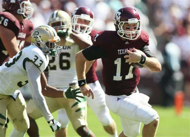 Texas A&M quarterback Ryan Tannehill, right, runs the ball against Baylor defender Josh Wilson, left, during the second half of an NCAA college football game, Saturday, Oct. 15, 2011, in College Station, Texas. Texas A&M won 55-28. (AP Photo/Jon Eilts) Photo: Jon Eilts, Associated Press / FR170396 AP