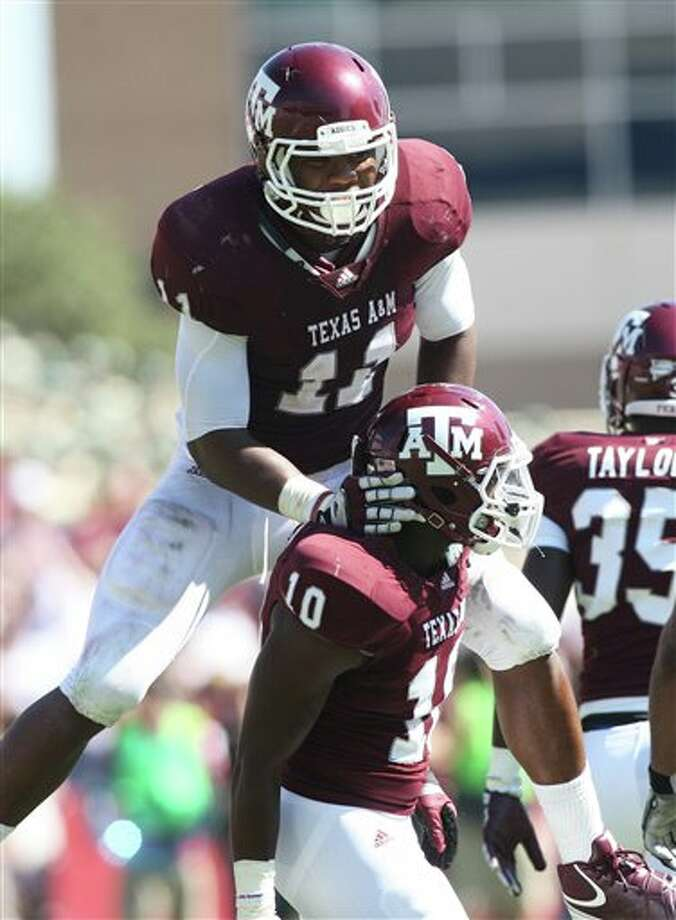 Texas A&M defenders Jonathan Stewart (11) and Sean Porter celebrate a 55-28 win over Baylor last season.  Jon Elits / Associated Press Photo: Jon Eilts, Associated Press / FR170396 AP