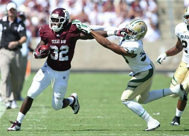 Texas A&M tail back Cyrus Gray (32) runs the ball against Baylor's Josh WIlson, right, during the second half of an NCAA college football game, Saturday, Oct. 15, 2011, in College Station, Texas. Texas A&M won 55-28. (AP Photo/Jon Eilts) Photo: Associated Press