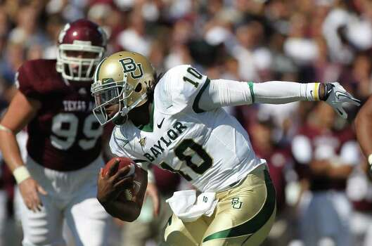 Baylor quarterback Robert Griffin III (10) tries t make Texas A&M defenders miss him as he  runs with the ball during the first quarter of a NCAA football game at Kyle Field, Saturday, Oct. 15, 2011,  in College Station. Photo: Nick De La Torre, Houston Chronicle / © 2011  Houston Chronicle