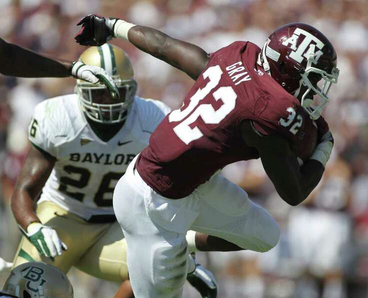 Texas A&M running back Cyrus Gray (32) spins out of the grasp of a host of Baylor defenders during t