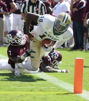 Texas A&M defensive back Terrence Frederick (7) stops Baylor quarterback Robert Griffin III (10) from scoring a touchdown during the third quarter of a NCAA football game at Kyle Field, Saturday, Oct. 15, 2011,  in College Station. Texas A&M won 55-28. Photo: Nick De La Torre, Houston Chronicle / © 2011  Houston Chronicle