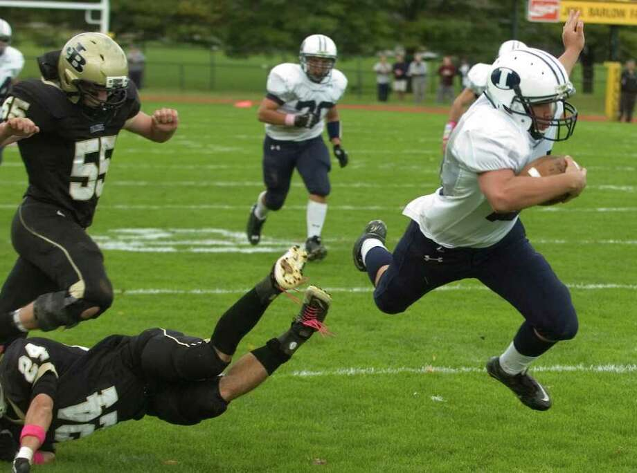 Joel Barlow's Andrew Bindelglass, bottom, left #24, knocks Immaculate's James Coppolla, right, off his feet during their game at Joel Barlow High School in Redding on Saturday, Oct. 15, 2011.  Barlow won 48-12. Photo: Jason Rearick / The News-Times