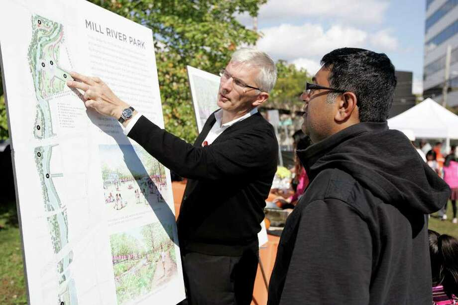Allen Spuleck of OLIN shows Stamford resident Prakash Wadhwani the plans for the new Mill River Park in Stamford at My Park Day. The 12-acre park is in its first phase of construction. Photo: J. Gregory Raymond / J. Gregory Raymond/Stamford Advocate Freelance