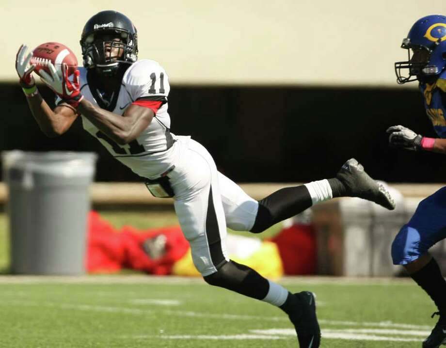 PA Memorial's Jhajuan Seales (left) makes a leaping reception past Channelview's Anthony Galvan during the first half of a high school football game, Saturday, October 15, 2011 at Stallworth Stadium in Baytown. Photo: Eric Christian Smith, For The Chronicle
