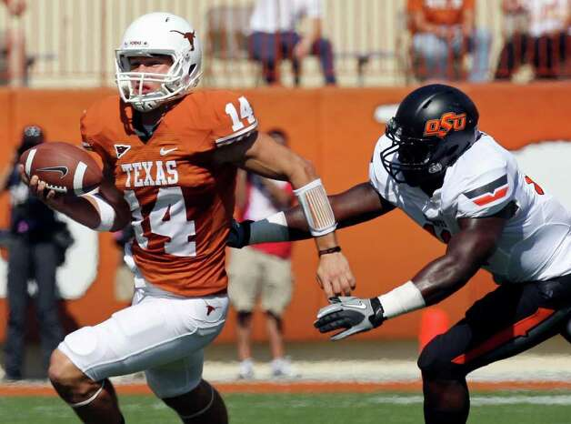 Texas' David Ash scrambles away from Oklahoma State's Shaun Lewis during first half action Saturday Oct. 15, 2011at Texas Memorial Stadium in Austin, Tx. Photo: EDWARD A. ORNELAS, Express-News / © SAN ANTONIO EXPRESS-NEWS (NFS)