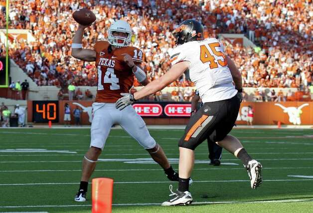 Texas' David Ash passes under pressure from Oklahoma State's Caleb Lavey during second half action Saturday Oct. 15, 2011at Texas Memorial Stadium in Austin, Tx. Oklahoma State won 38-26. Photo: EDWARD A. ORNELAS, Express-News / © SAN ANTONIO EXPRESS-NEWS (NFS)