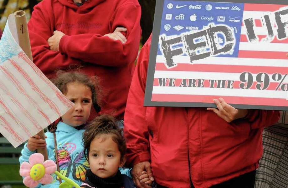 Five-year-old Julia Davis,left, and her two-year-old sister Sarah Davis attend the Occupy Albany protest with their grandmother Lily Rodulfo at the Capitol in Albany, NY Saturday Oct. 15, 2011.( Michael P. Farrell/Times Union) Photo: Michael P. Farrell