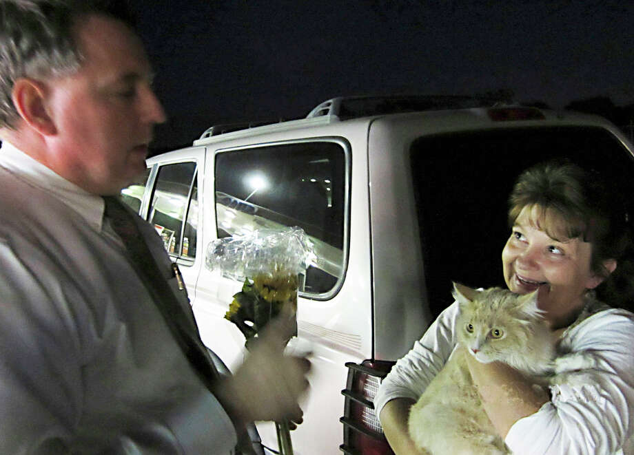 Dennis Conrad (left) reunites Squeek the cat with his owner Brenda Baird, who drove 700 miles to retrieve her pet. Squeek leapt from her arms when her family stopped at Camp Bullis Road for gas in September on the way from North Carolina to New Mexico. Photo: Vincent T. Davis/vtdavis@express-news.net / CAT REUNION VINCE T. DAVIS