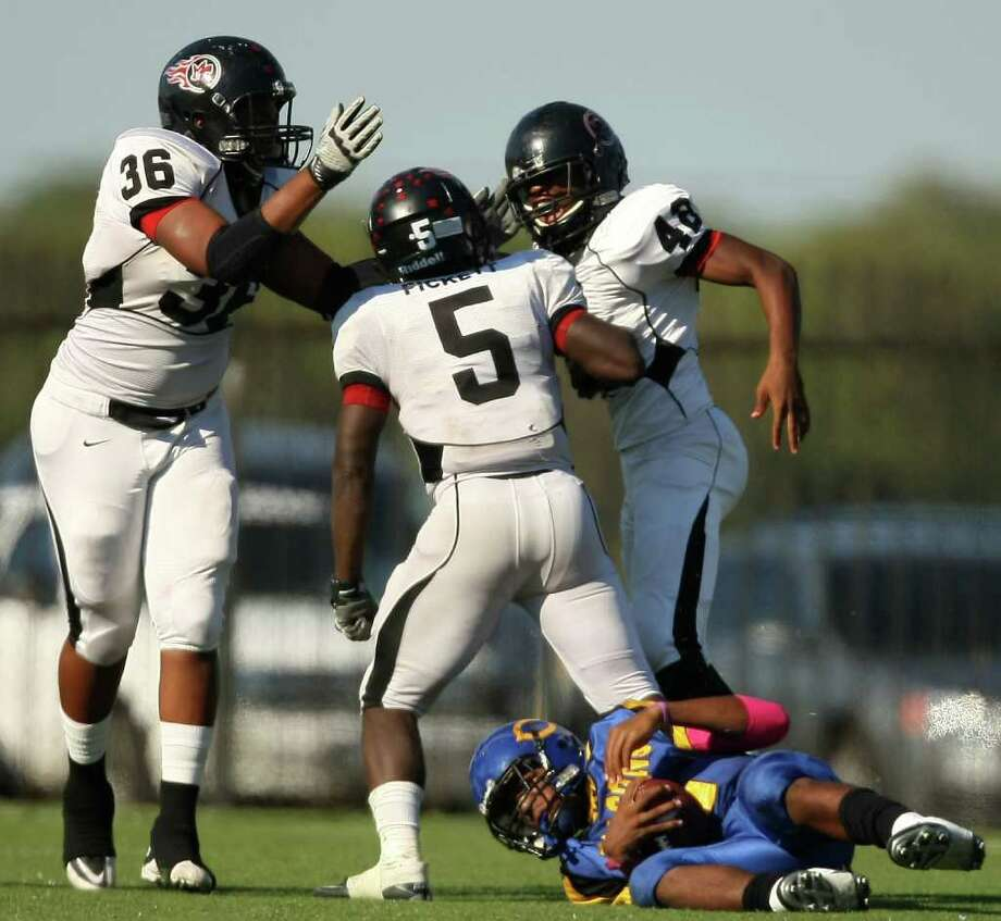 Joshua Pickett (5) is congratulated by teammates Donovan Banks (left) and Melbrodrick Matthews after Pickett's sack of Channelview's Averion Hurts (2)during the second half of a high school football game, Saturday, October 15, 2011 at Stallworth Stadium in Baytown. Photo: Eric Christian Smith, For The Chronicle