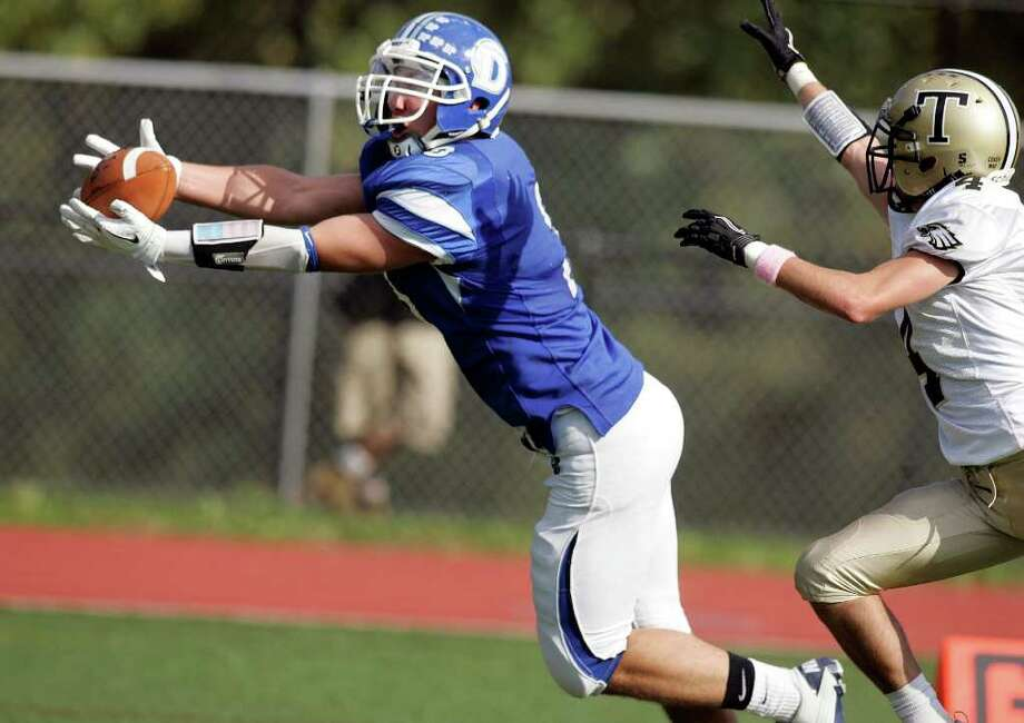 Darien wideout Matthew Forelli catches the first of his two touchdown receptions during an FCIAC battle against Trumbull High School on Saturday in Darien. Covering on the play is Jeff Jaboe. Darien won the game 21-0.  © J. Gregory Raymond Photo: J. Gregory Raymond / J. Gregory Raymond/Stamford Advocate Freelance