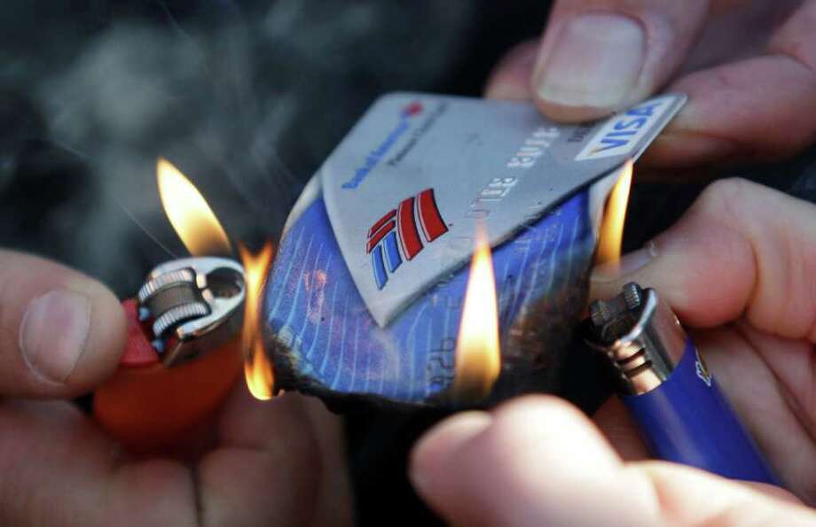 "Protesters with the ""Occupy Seattle"" movement burn a Bank of America debit card as they protest, Saturday, Oct. 15, 2011, in downtown Seattle. Photo: AP"