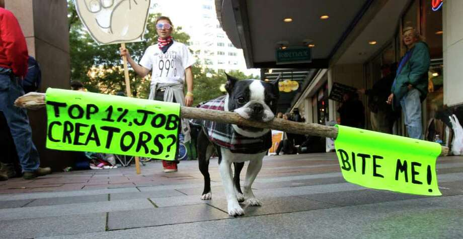 """Mugsy,"" a Boston Terrier, carries a sign that reads ""Top 1%, Job Creators? Bite Me!"" during an Occupy Seattle protest, Saturday, Oct. 15, 2011, in downtown Seattle. Mugsy was there with owner Frankie Petitclerc, of Whidbey Island, Wash. Photo: AP"