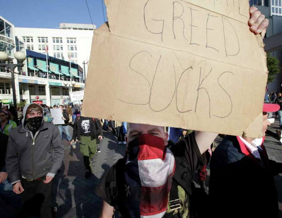 "A protester with the ""Occupy Seattle"" movement carries a sign that reads ""Greed Sucks"" during a march, Saturday, Oct. 15, 2011, in downtown Seattle. Photo: AP"