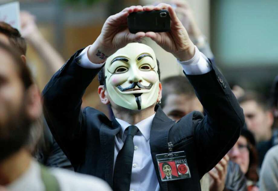 "A protester with the ""Occupy Seattle"" movement wears a Guy Fawkes mask and takes a photo with a mobile phone as he demonstrates, Saturday, Oct. 15, 2011, in downtown Seattle. Photo: AP"